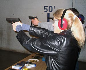 Heather Bosch practice firing a hand gun during NRA certification training for her series Taking Up Arms